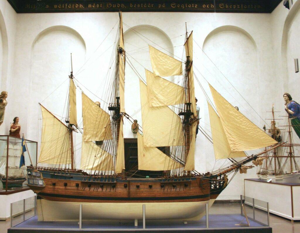 Modell av gammalt segelfartyg med vitt skrov och hissade vita segel.