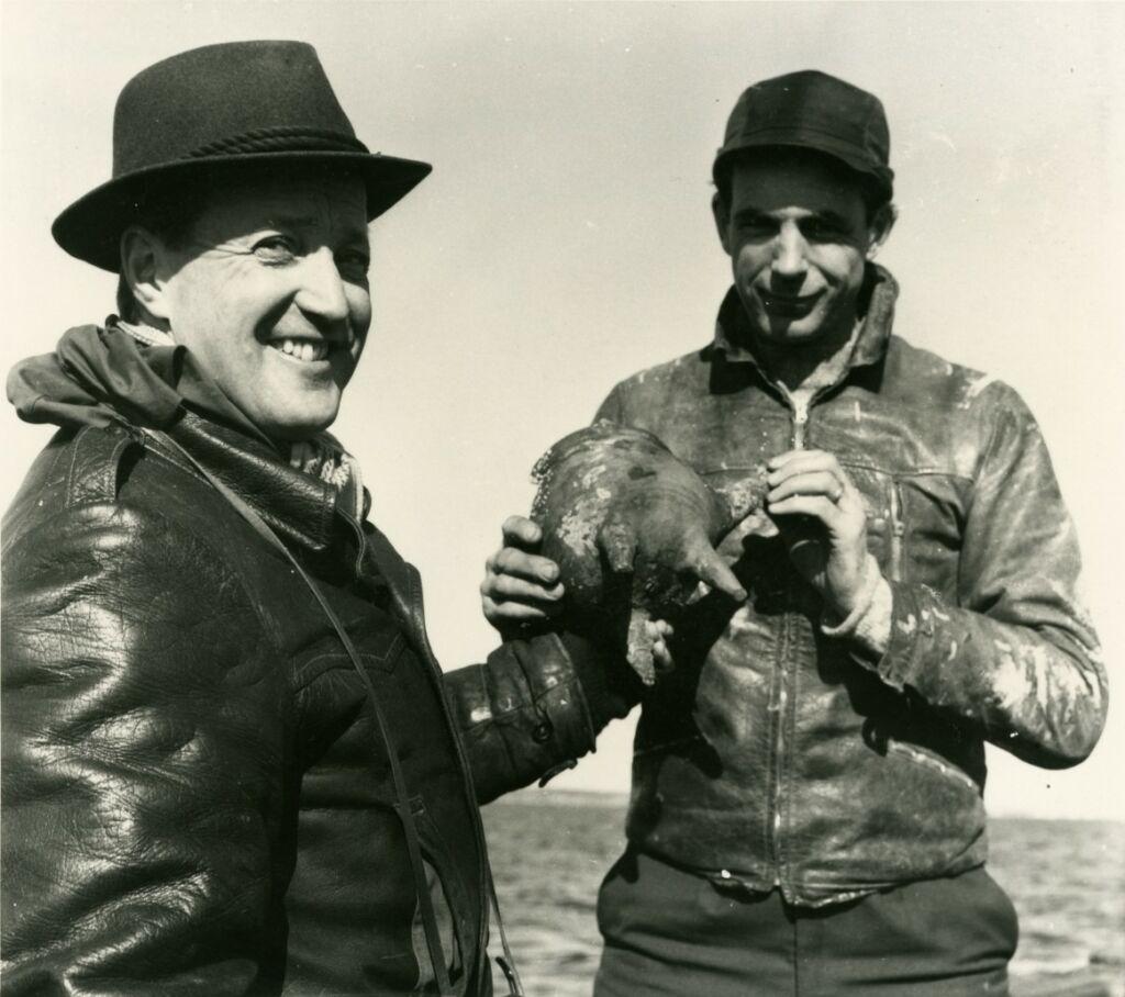 Svartvitt foto av två leende män, en i läderjacka och hatt och den andre i mössa och läderjacka, båda hållandes ett föremål