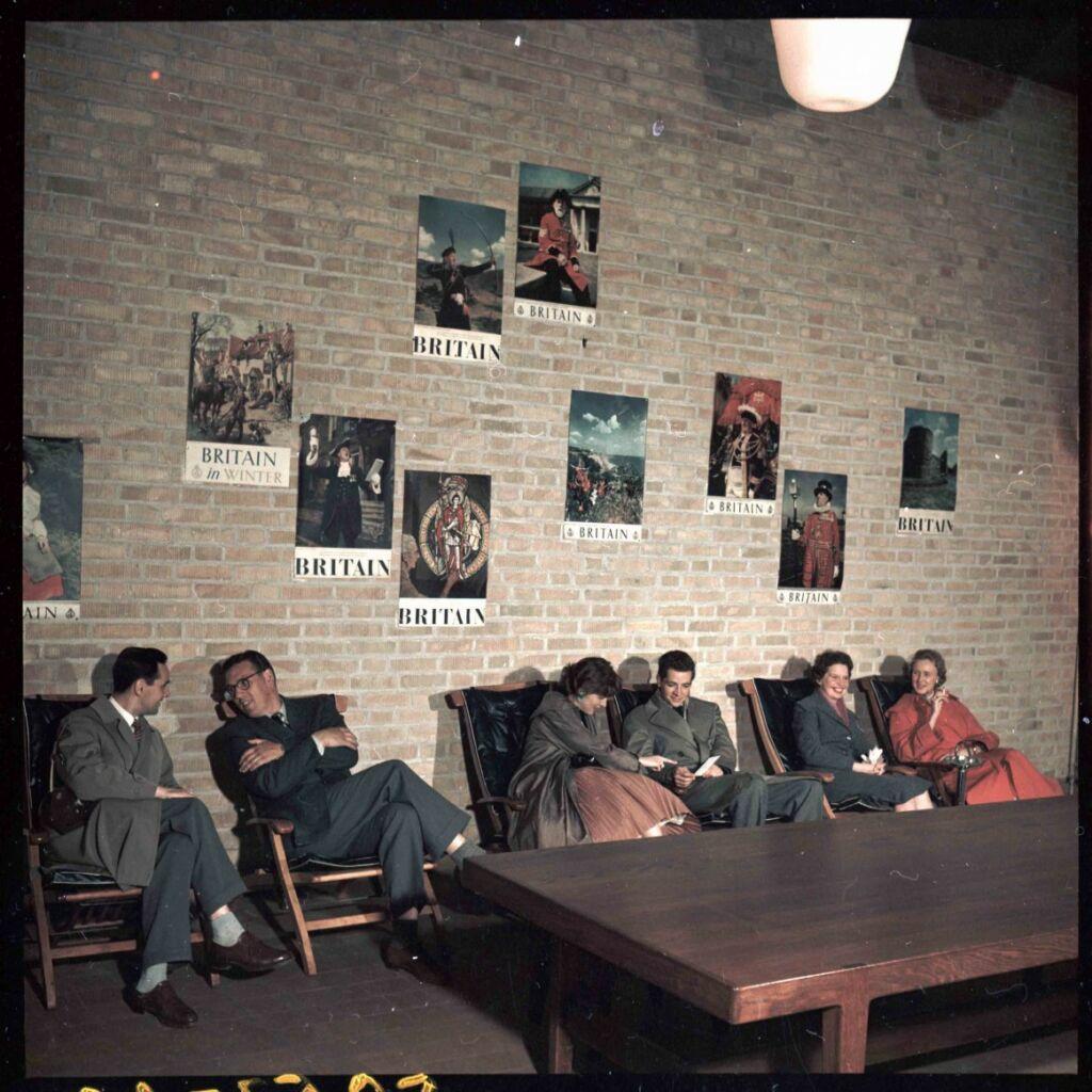 Passagerare väntar i stolar i vänthall med murad vägg med affischer om resmål.