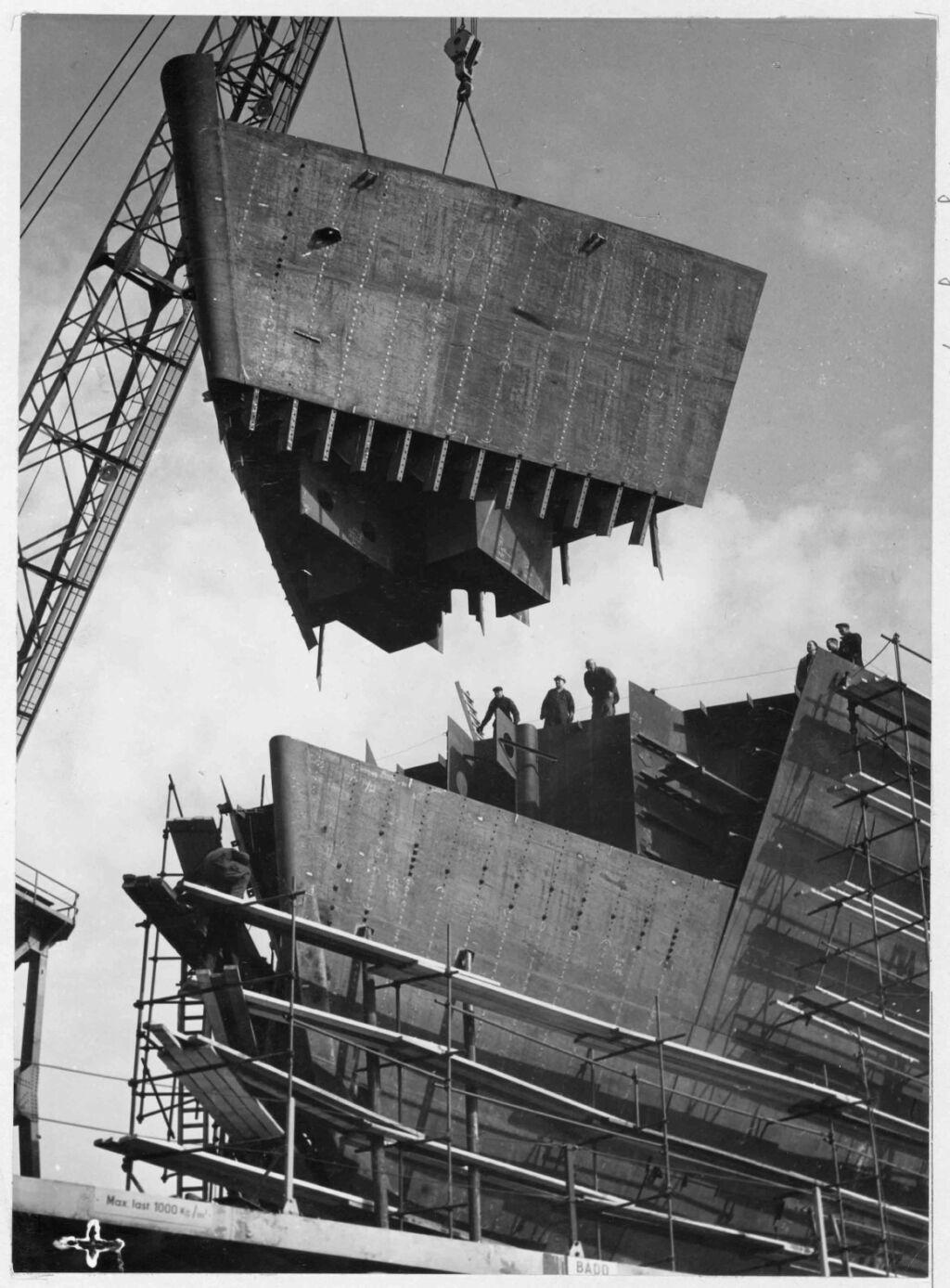 Svartvitt foto av fören på ett fartyg som hissas ner av stor kran vid bygge på ett varv.