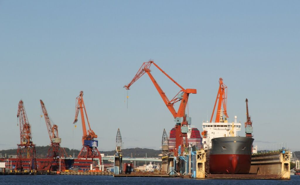 Orange kranar mot blå himmel, ett fartyg ligger i en docka.