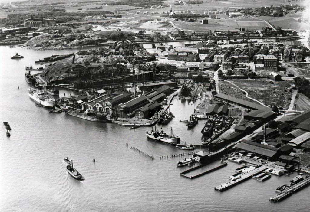 Svartvitt flygfotografi som visar en hamndel fylld med båtar, kajer och bryggor.